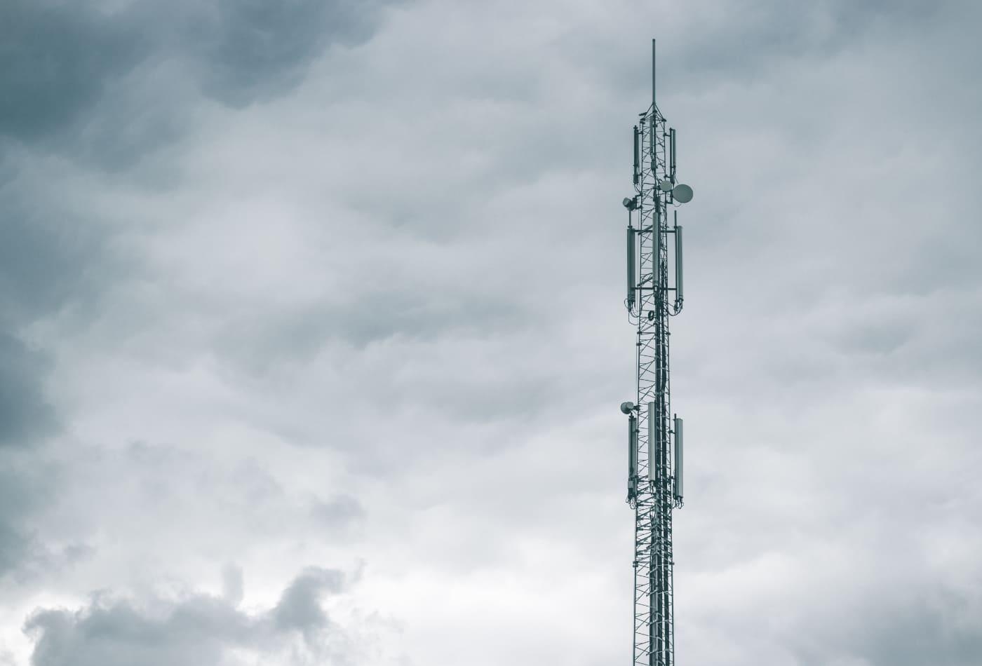 Funkmast mit dunklen Wolken im Hintergrund; Telekommunikation