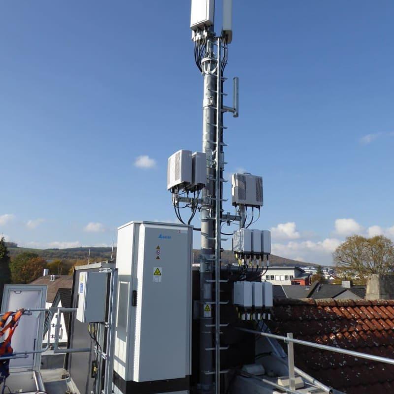 Telekommunikationsturm auf einem Dach - Rollout Mobilfunk