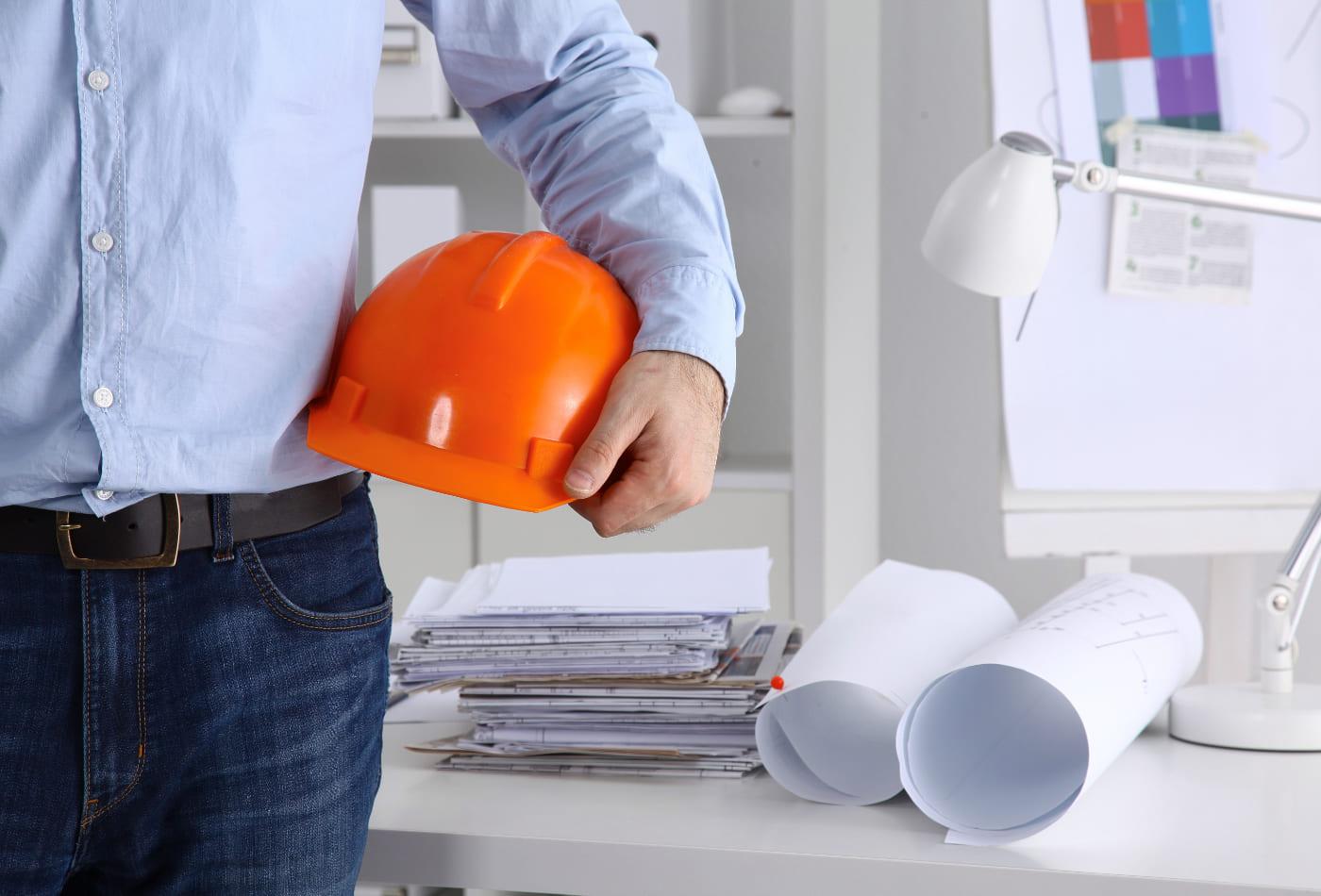 Bauleiter mit Helm und Bauplänen